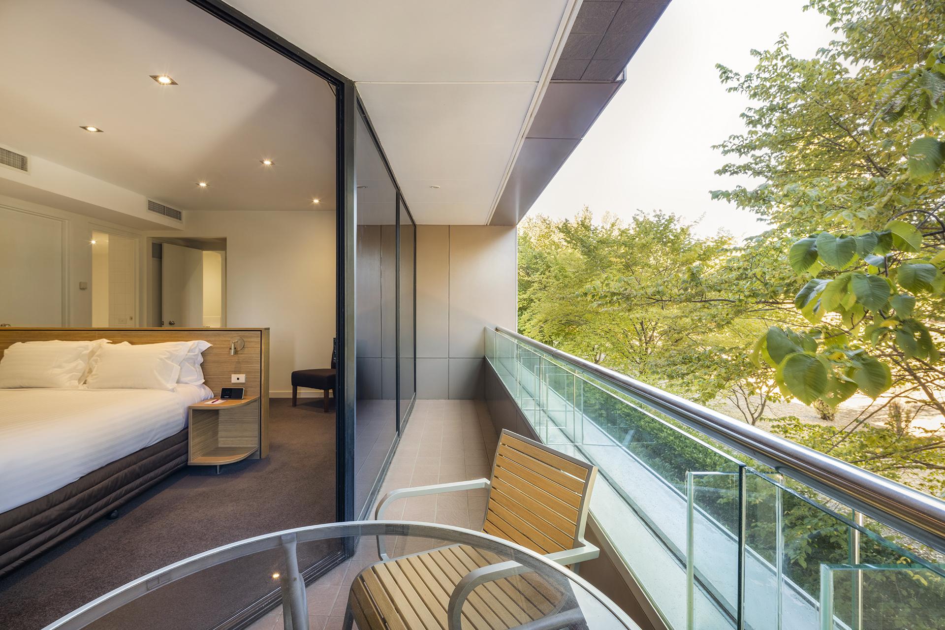 The Deluxe Suite bedroom with balcony overlooking Glebe Park.