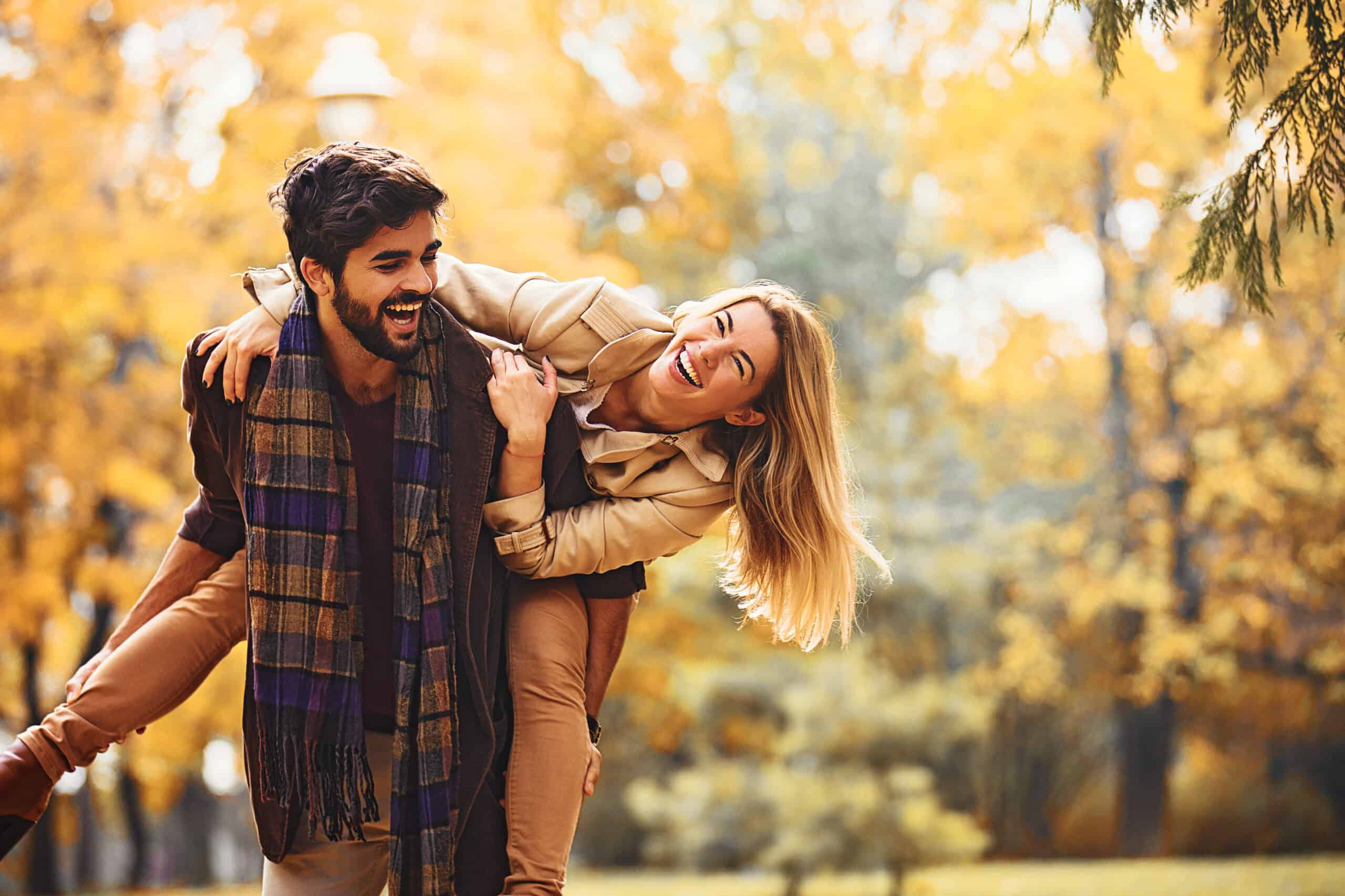 couple laughing and playing in fall foliage, autumn